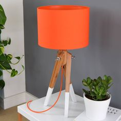 One of our Orange pick and mix lampshades with a matching orange lining on our bamboo and white dipped leg table lamp base.