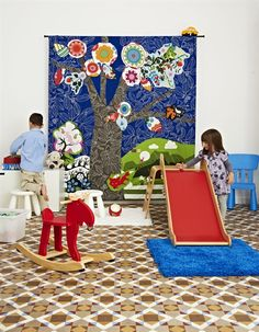 Beautiful kids play space - love the wall hanging, wooden toys and gorgeous vintage floor tiles