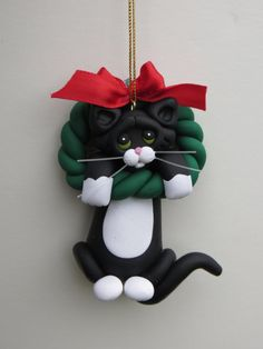 Here is a black tuxedo cat hanging from a Christmas wreath.    This unique ornament measures 3 inches long and 2 inches wide and is made from a mixture of polymer clays.    Also, all of my figurines come with a gift box so all you have to do is wrap some ribbon around the box and you are ready to give a special keepsake for the dog or cat lover in your life.    If you have any questions regarding my ornaments and figurines please let me know. I always enjoy input from my customers as it…