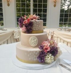 Tiered cake with monogram and flowers. Find wedding cake info here: http://www.realbuttercream.com/cakes/unique-wedding-cakes.html