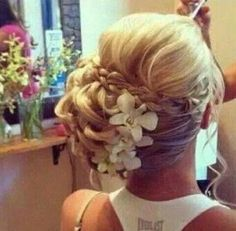 Side pinned up bun with a braid and flowers.