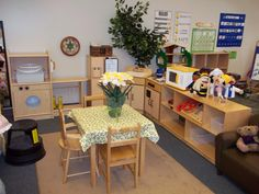Dramatic Play Area. I like the angled shelving, and plant in the corner.
