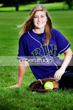 Senior photo on the field with her softball gear.