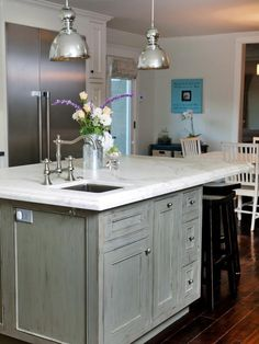 The light gray kitchen island contrasts with and complements the dark wood flooring.