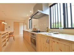 1F:キッチン<br /> 2人で料理をしても余裕の広さ。食卓の並びに配膳に便利な作業台を造付けました。