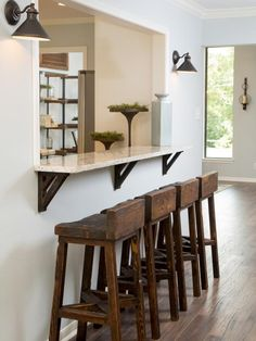 A window was cut between the living room and kitchen to create a breakfast bar with granite countertops and handmade bar stools, as seen on HGTV's Fixer Upper.