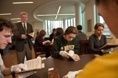 Bill Hyland (Center for Norbertine Studies) and students look at copies of St. Augustine's Confessions dating back to as early as the 17th century.