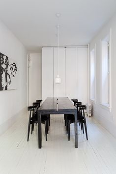 A Pair of Designers Renovate Their Brooklyn Brownstone With a Bright Monochromatic Palette - Photo 10 of 12 - Elbow chairs by Hans J. Wegner for Carl Hansen & Søn surround a table of the couple's own design. By removing walls in this space, extra storage was possible. The trio of A330S pendants are by Alvar Aalto for Artek. The painting, The Look, is by Ed Parker.