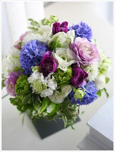 紫のラナンキュラスやヒヤシンス、チューリップなどの春の花にハーブをたっぷり合わせたナチュラルなブーケ。spring purple clutch bouquet ranunculus hyacinthus