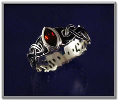 Celtic Fire Ring - Intricate Celtic knotwork combines sterling silver with black enamel for a stunningly effective design. A sparkling red garnet takes center stage, to add a spark of passion.