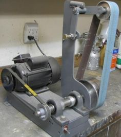 Belt Grinder Homemade belt grinder constructed from a 1hp motor, steel plate, bearings, and cast wheels