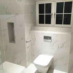 Bathrooms walls and floor tiled with Carrara marble look thin porcelain tiles. #marble #porcelain #tiles