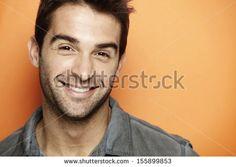 Portrait of mid adult man smiling against orange background - stock photo