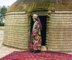 1907-1915  Prokudin-Gorksii captures the traditional dress, jewelry and hairstyle of an Uzbek woman standing on a richly decorated carpet at the entrance to a yurt, a portable tent used for housing by the nomadic peoples of Central Asia.