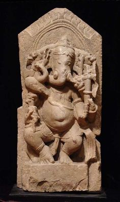 Northern India, c. 10th-12th century AD. Ganesh, the elephant god, depicted garlanded and crowned seated on his throne with attributes, his large male member hanging below, a flaming halo above.