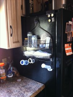 Bottle station out of shower caddy mounted with Command hook onto fridge, great for my small kitchen! CDF
