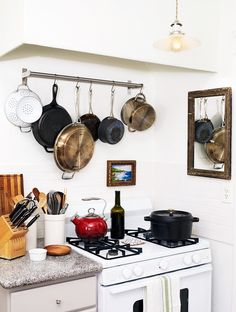 Bright kitchen with hanging pots and pans storage, white stove, rustic mirror and framed artwork.