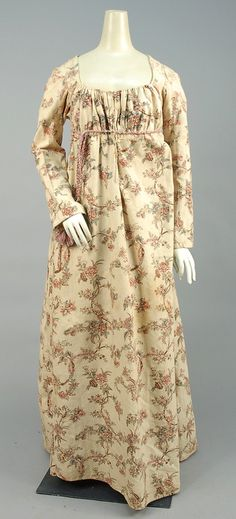 Printed cotton gown, cream with scrolling polychrome floral having long sleeve, gathered bodice, high waist with belt loops, flared skirt pieced side gores, muslin bodice lining with front closure 1800-1805