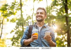 stock-photo-happy-hipster-man-walking-in-the-park-smiling-and-drinking-orange-cocktail-bearded-man-in-jeans-321156677.jpg (450×320)