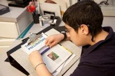 Boy uses handheld magnifier to read a line of print.