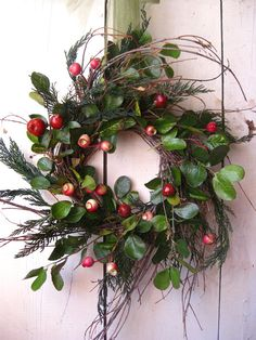 A classic holiday wreath charms with the grace of the Colonial period! A birch branch base is adorned with preserved, fragrant cedar and faux hawthorn leaves. Lifelike, faux rosehips add a pop of seasonal color. The wreath measures approximately 22 inches from tip to tip with an interior measurement of about 5 inches. It is suspended by a green satin ribbon and a festive bow. *Please note that the ribbon described is not shown in the photo.  This wreath would be a stunning winter or holiday…