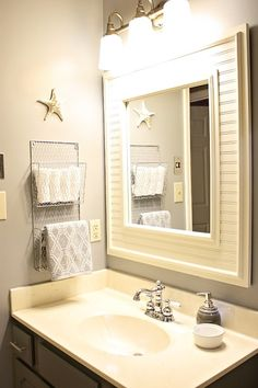 hand towel holder idea.  Like putting wood around the mirror, new lights, and the hand towel holder.