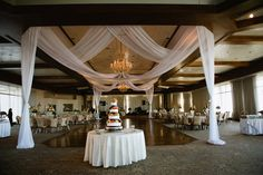 """Andy Tolar of www.designproductionsllc.com created a stunning appearance for the Ballroom at The Club. As guests entered, the first thing they saw was the beautiful bride's cake from Magnificent Cakes which was framed beautifully with the sheer drape from Design Productions. The drape was hung from the ceiling in a criss-cross pattern and draped to the floor to create """"four corners"""" 
