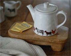 """Make time for tea time in your cozy farmhouse kitchen! Our Farmstead Teapot features illustrations of some favorite barnyard friends: pig, cow, goat and chicken. Holds four cups. White ceramic. 8.5""""L x 5.75""""H. Coordinates with our Farmstead Sugar and Creamer Serving Set"""