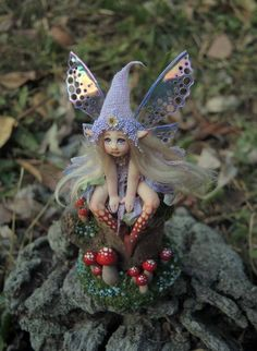 Greetings Fairy Lover! This super cute (and very tiny) little fairy is sculpted by me from polymer clay. She is dressed in hand dyed silks, faux moss, tiny iridescent beads, has hand painted stockings, hand made iridescent wings,a hand made muslin hat and hand made eyes. She has flaxen blonde hair and sits on her woodland scene thats been decorated in hand sculpted mushrooms, faux moss and tiny beads and which she is removable from. She is an original one of a kind creation hand sculpted…
