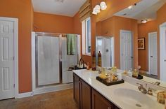 I like the orange walls in this master bath.  Precast fiberglass shower has built in bench seat and soap dish.