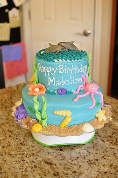 """M's """"dolphin"""" cake - buttercream frosting, brown sugar """"sand"""", seashell mold used to make seashell decorations from colored chocolate melts, MMF animals and coral, dolphin figurines topper"""