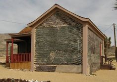 GLASS BOTTLE HOUSE -  Houses constructed from recycled glass bottles are not a recent innovation and Tom Kelly's bottle house in Ryolite, Nevada was constructed from 51,000 glass bottles back in 1920. The air in the bottles is a great insulator.