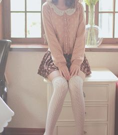 A very cute and more innocent look with the pastel pink sweater with the white peter pan collar, patterned skirt, and knee high socks.