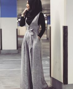 Grey jumpsuit, black shirt, black scarf, watch