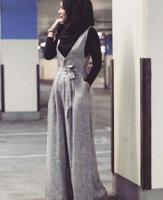 Grey jumpsuit, black shirt, black scarf, watch