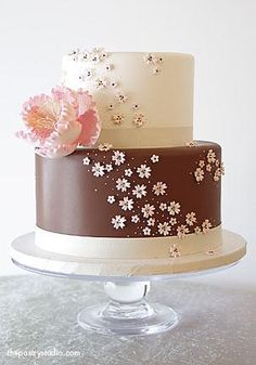 a chocolate and brown celebration cake with sugar paste cherry blossoms and a large peony flower.  s