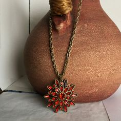 A Large Gold Chain holding a Large Flower with Red Petals by kaysjewelrydesign on Etsy