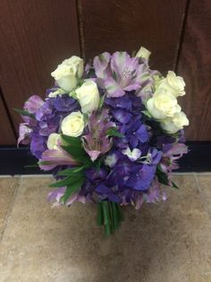 Purple and white beach bridal bouquet with purple hydrangea, lavender alstroemeria lilies, white spray roses, and dark purple satin ribbon by #SunshineFlorist