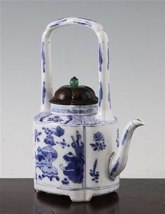 A Chinese blue and white wine pot, Kangxi period, of quatre-lobed form, painted with panels of objects, flowers and rockwork, on four shaped bracket feet, later rosewood cover with hardstone and silver finial, 19cm