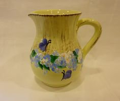 This pale yellow ceramic pitcher has been hand painted with a design of blue and white daisies, green leaves and dark blue purple butterflies.