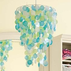 Transform your space into a tropical oasis with this Capiz Chandelier shade. Rows of delicate capiz shells in tonal colors dangle from a circular frame, just waiting to catch the next breeze. Ocean Bedroom, Mermaid Bedroom, My New Room, My Room, Capiz Shell Chandelier, Mobile Chandelier, Shell Lamp, Nursery Lighting, Nursery Chandelier