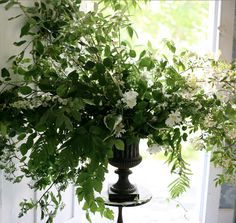 Lots of interesting foliage and pretty white flowers in this natural styled floral urn