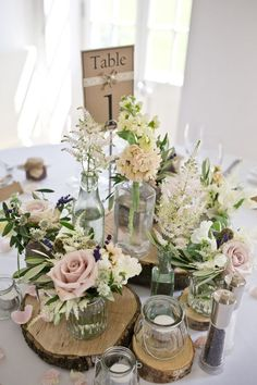 centrepiece of rustic tree slices with jars of pink flower stems / http://www.deerpearlflowers.com/unique-wedding-centerpiece-ideas/2/