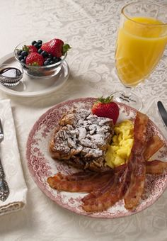 French toast casserole with bacon, scrambled eggs and fresh fruit including red strawberries and blue berries.