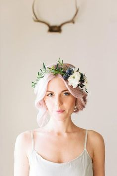 A floral crown looks beautiful against pastel hair, perfect for brides with a bohemian style.