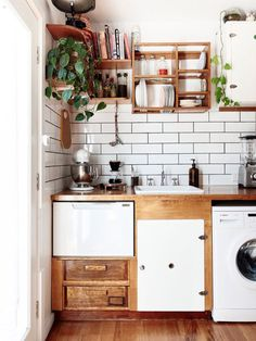 Dream kitchen with butcher block countertop, exposed shelving, indoor plants, subway tiles, and a hanging dish rack
