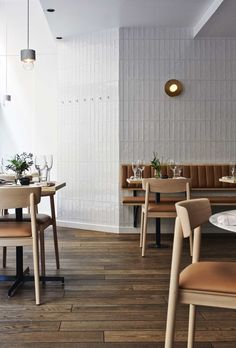 could we tile the entry wall?  Tan cushion on white bench and brass wall light.     Michel Restaurant Helsinki by Joanna Laajisto | Yellowtrace