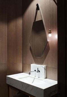 Wood-panel-clad powder room with marble sink. Design by Kerry Phelan Design Office and Chamberlain Javens Architects.