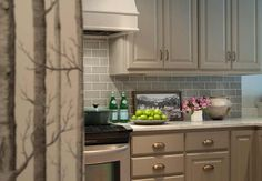 Taupe and grey kitchen features taupe cabinets adorned with brass cup pulls paired with white marble countertops and a gray subway tiled backsplash.