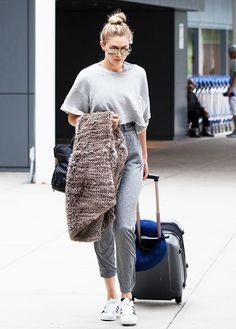 Gigi Hadid wears a gray top, gray sweatpants, Adidas sneakers, aviator sunglasses, and a furry blanket airport style
